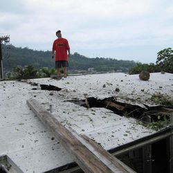 """FILE - In this April 13, 2012 file photo, John """"Keoni"""" Maemori's stands on the roof of his house while looking at the hillside above in the Kalihi neighborhood of Honolulu after a boulder crashed into it. The state Board of Land and Natural Resources is calling an emergency meeting for authorization to enter private property where boulders rolled down a Honolulu mountainside and crashed into houses."""