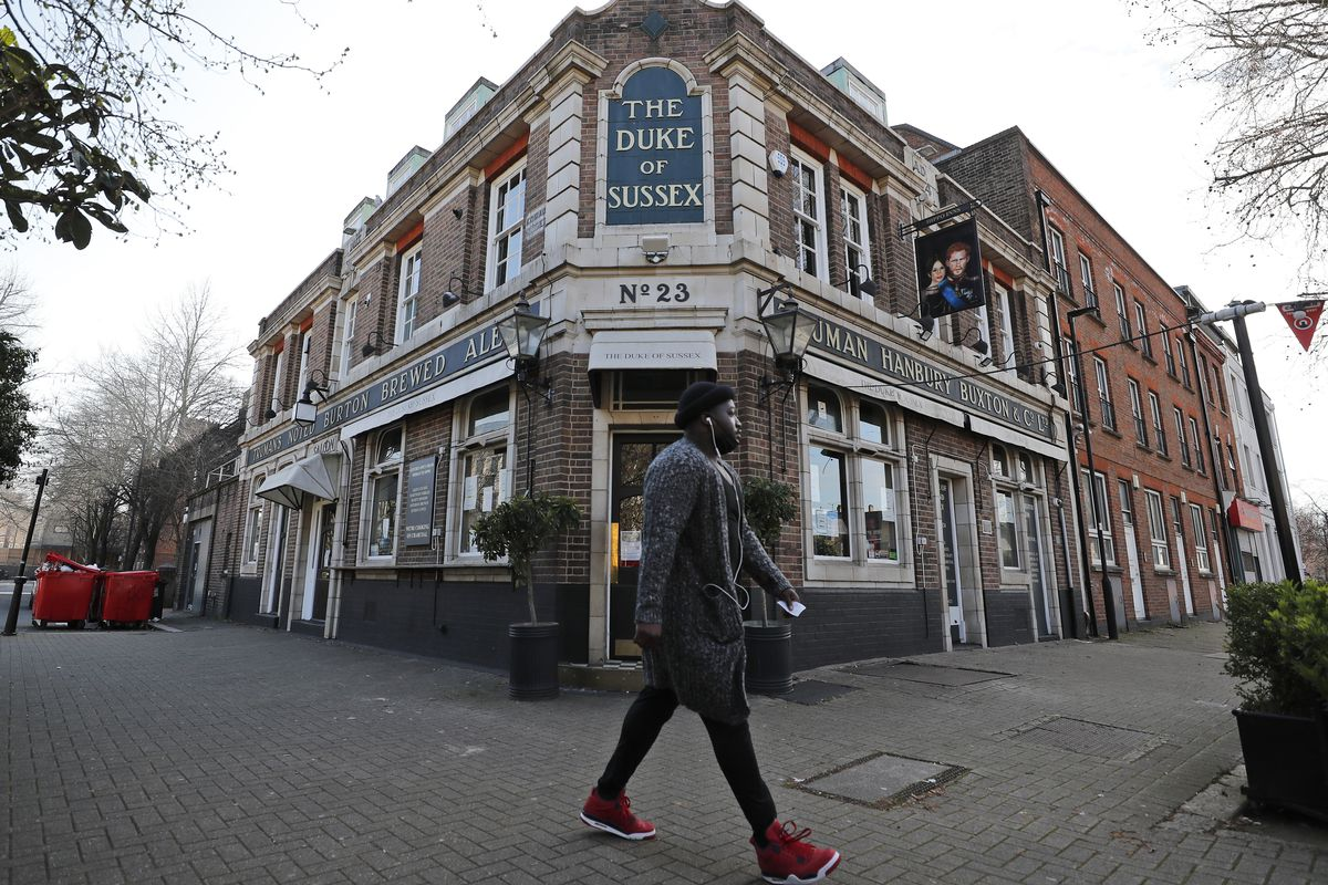 A man walks past the Duke of Sussex pub with a sign depicting the image of Britain's Prince Harry and his wife Meghan, near Waterloo station, London, Tuesday March 9, 2021.