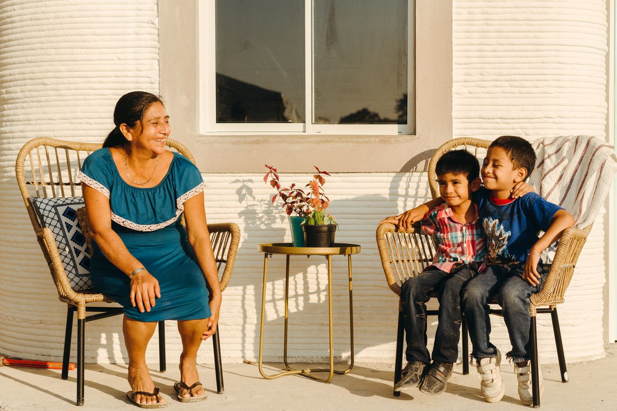 A woman and two kids sit in woven chairs on a porch.