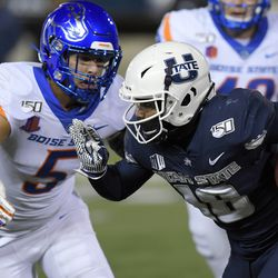 Utah State wide receiver Jordan Nathan (16) carries the ball as Boise State safety Evan Tyler (5) defends during the second half of an NCAA college football game Saturday, Nov. 23, 2019, in Logan, Utah.