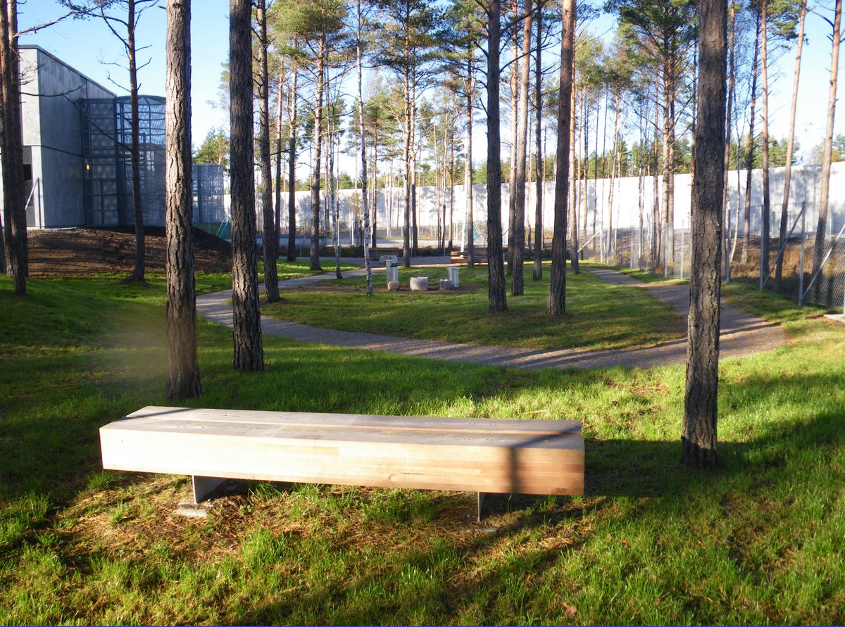 The grounds outside of the prison with trees and benches.