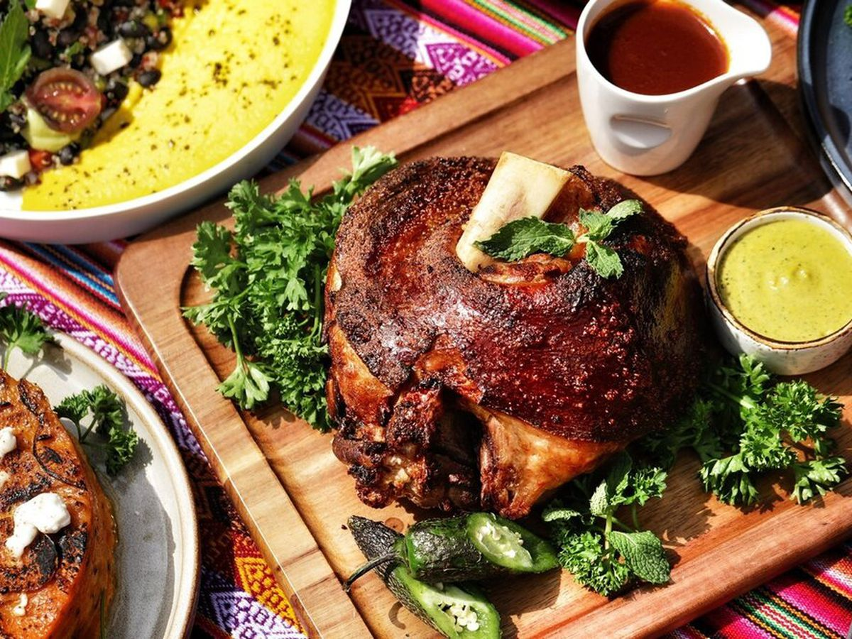 Crispy pork shank and other dishes spread out on a table.