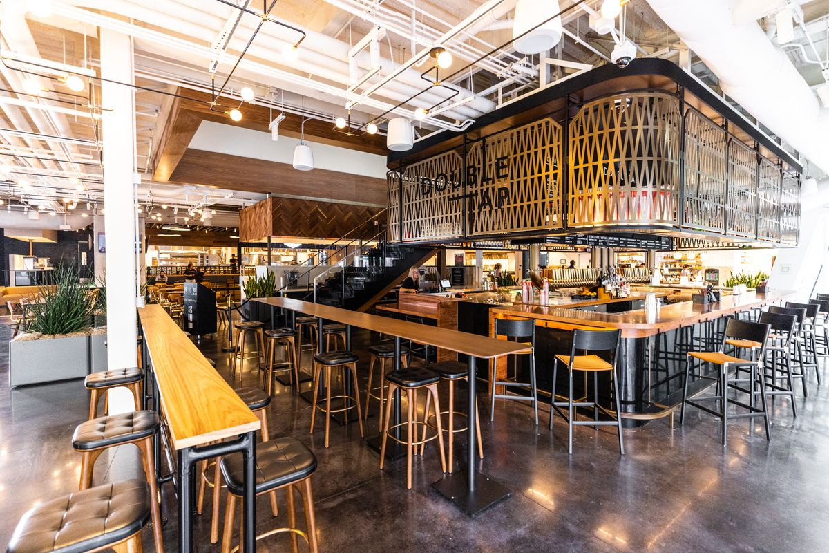 """A bar with black and natural wood seating and an ornate gold overhang that reads """"Double Tap"""""""