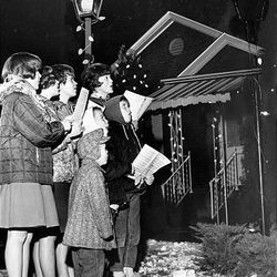 A group of young people singing Christmas carols in December 1963.
