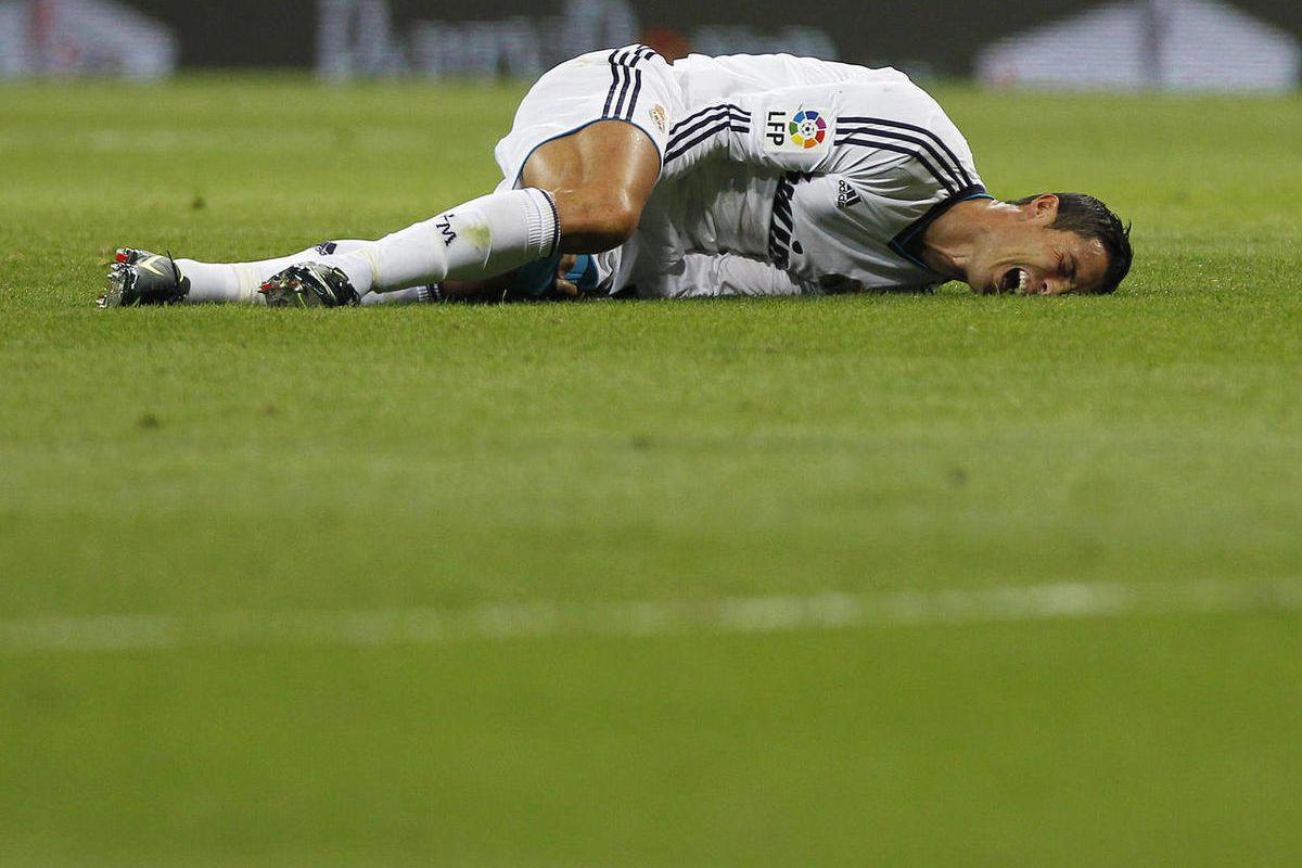 Real Madrid's Cristiano Ronaldo from Portugal reacts after receiving an injury during a Spanish La Liga soccer match against Granada at the Santiago Bernabeu stadium in Madrid, Spain, Sunday, Sept. 2, 2012.