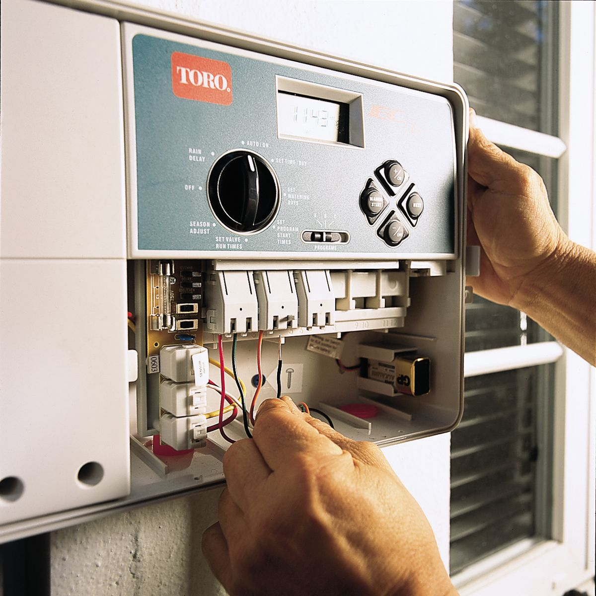 Man Attaching Wires to Timer Terminal For Sprinkler System