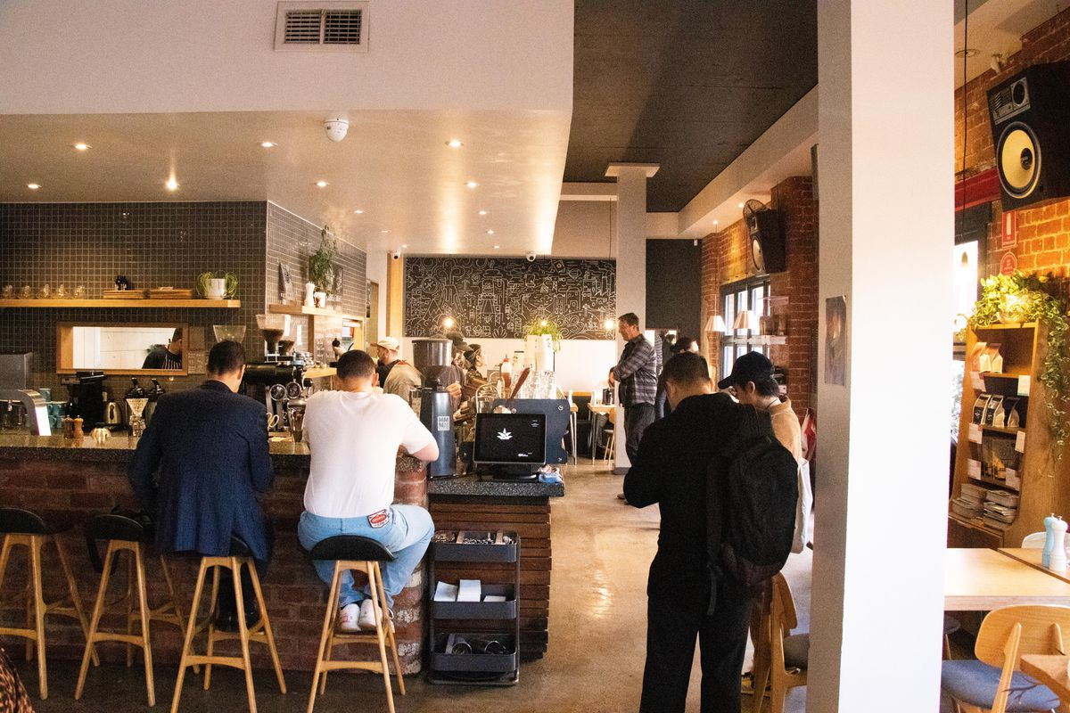 Inside a cafe, to men sit at a counter and other people wait for drinks by the coffee counter.