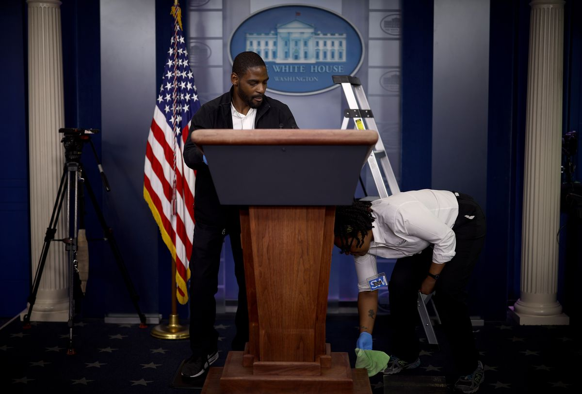 A man and woman in black and white uniforms clean the president's podium. The seal of the White House is behind them. They have on nitrile gloves, but no other form of PPE.
