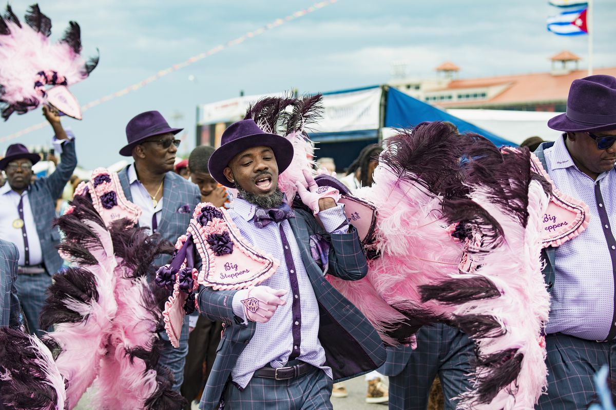 A group of men wearing pink feathers and purple hats and matching plaid suits strut by