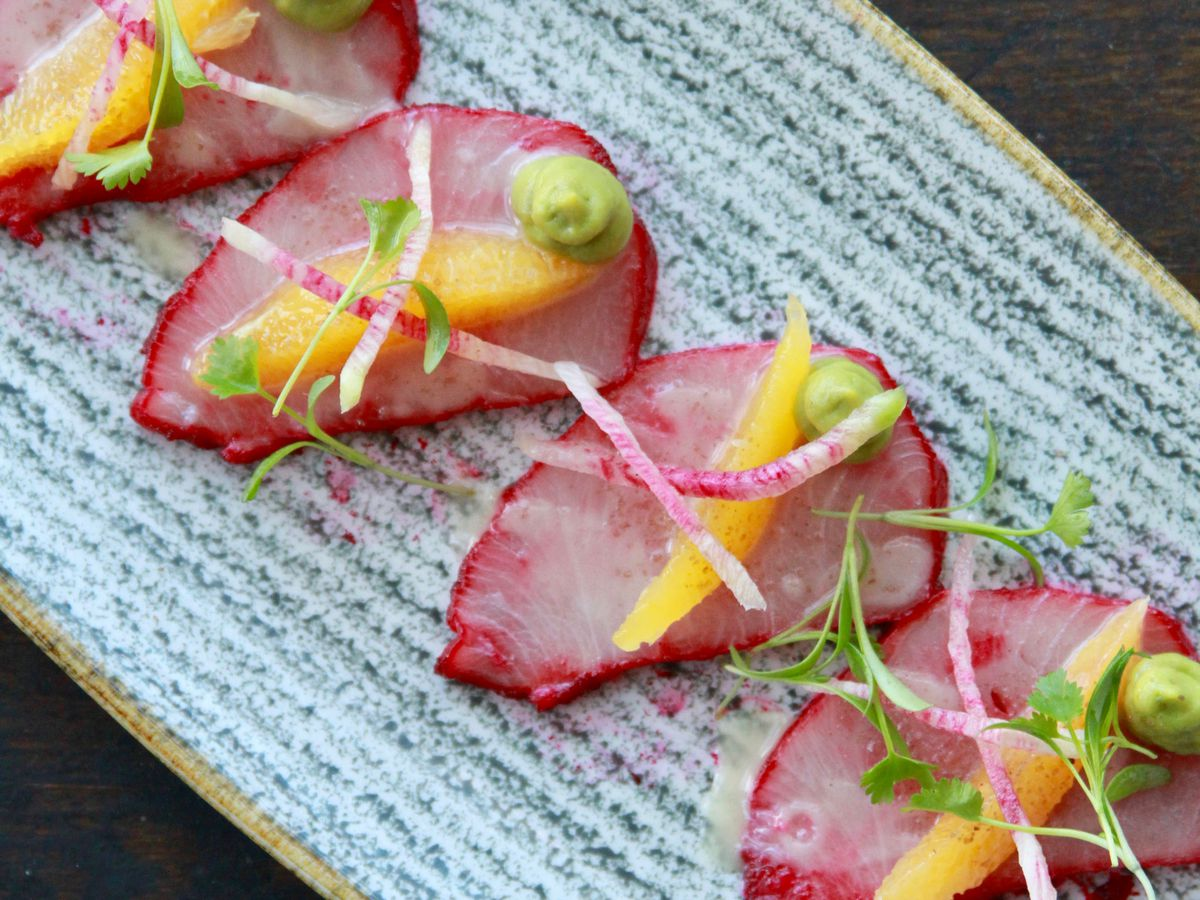 From above, a decorative platter with four slices of crudo dyed pink with matchstick radishes and wasabi paste for garnish
