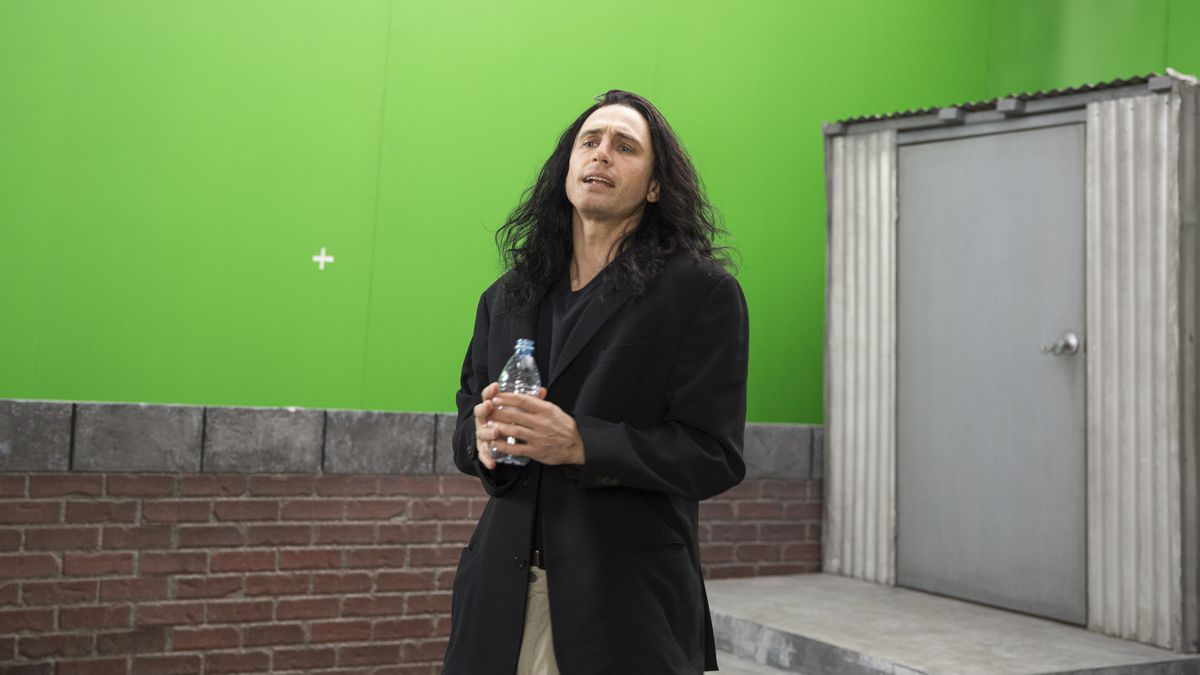 a man in a too big black jacket with long black hair in front of a green screen on a fake roof