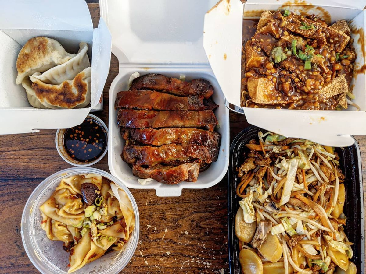Overhead view of takeout containers full of Chinese food spread over a wooden tabletop, including two types of dumplings, boneless spareribs, and more
