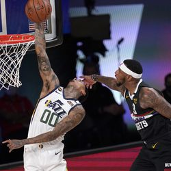 Utah Jazz's Jordan Clarkson (00) goes up for a shot as Denver Nuggets' Torrey Craig (3) defends during the first half an NBA first round playoff basketball game, Tuesday, Sept. 1, 2020, in Lake Buena Vista, Fla.