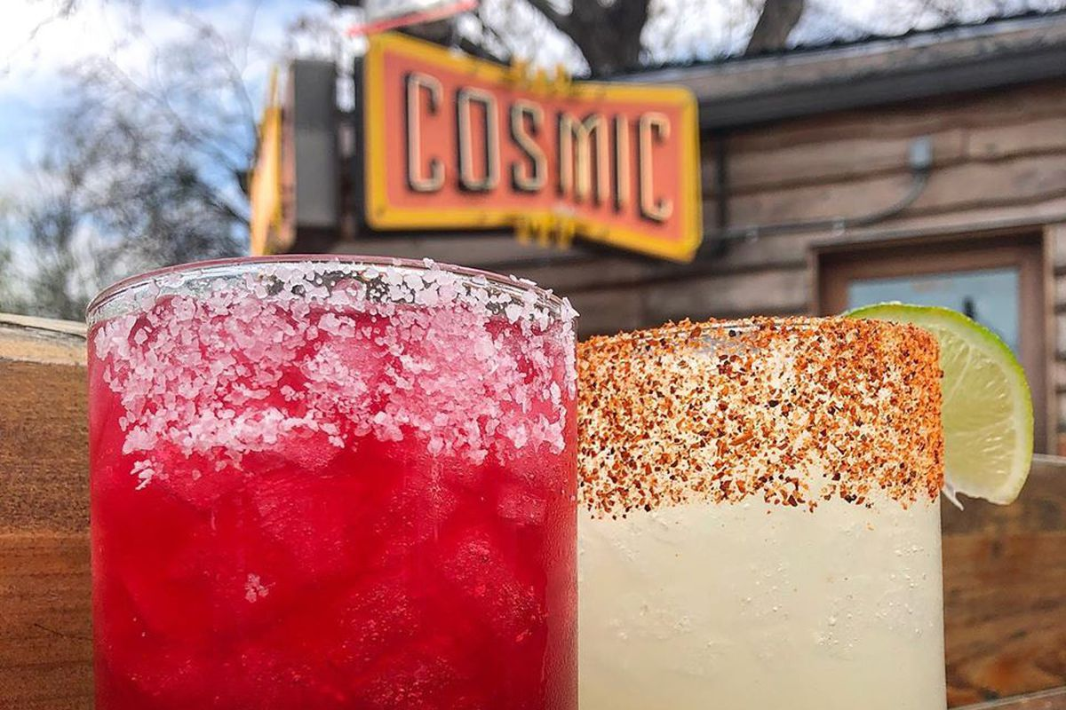 A red margarita with white salt and a green margarita with spicy salt on a wood table with the cosmic sign in the background