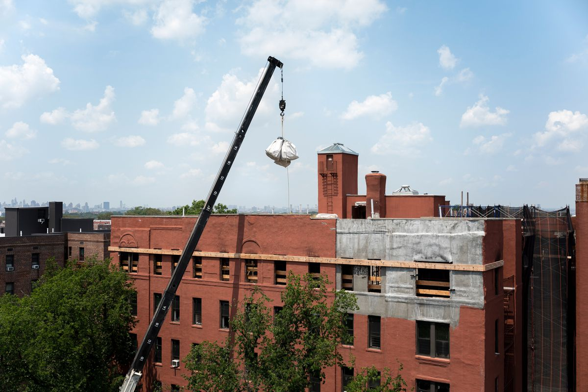A crane removes bags of debris from 89-07 34th Ave. in Jackson Heights. July 16, 2021.
