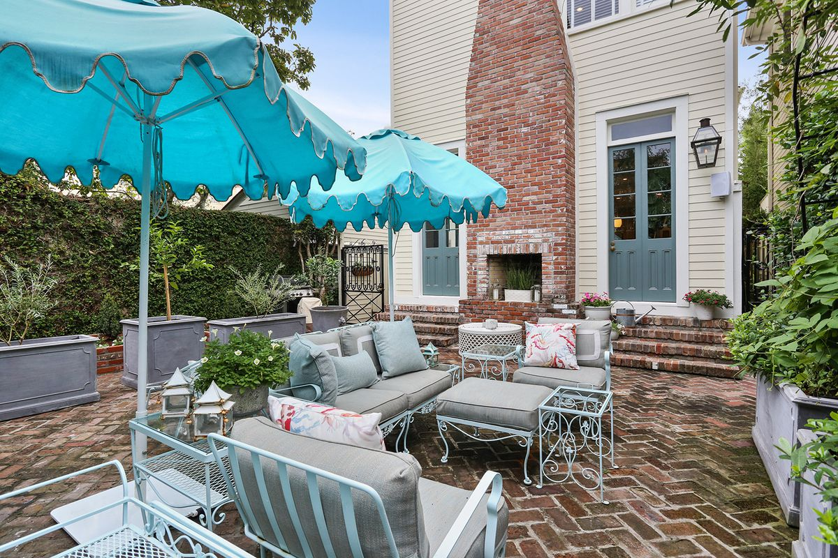 Rear patio with potted plants, brick floor, cushioned furniture and a brick fireplace