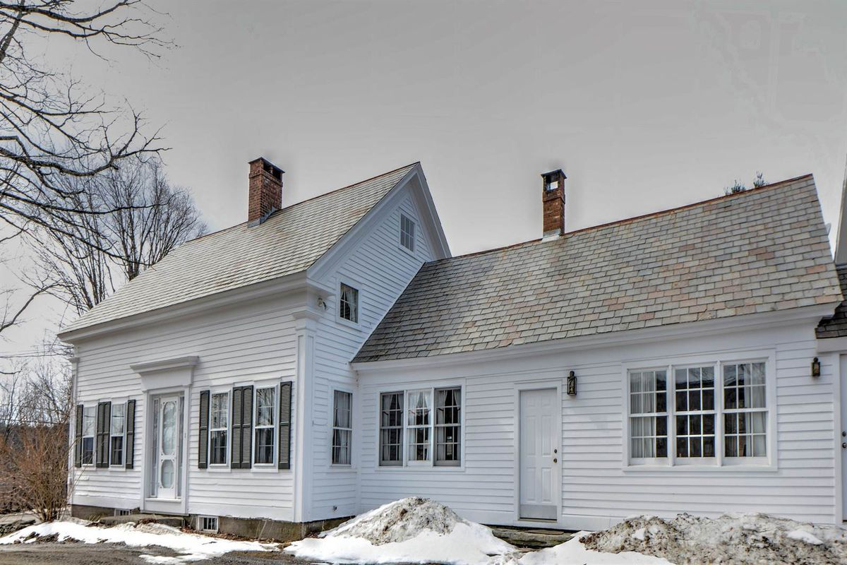 Wood-framed colonial house with side house on snowy land.