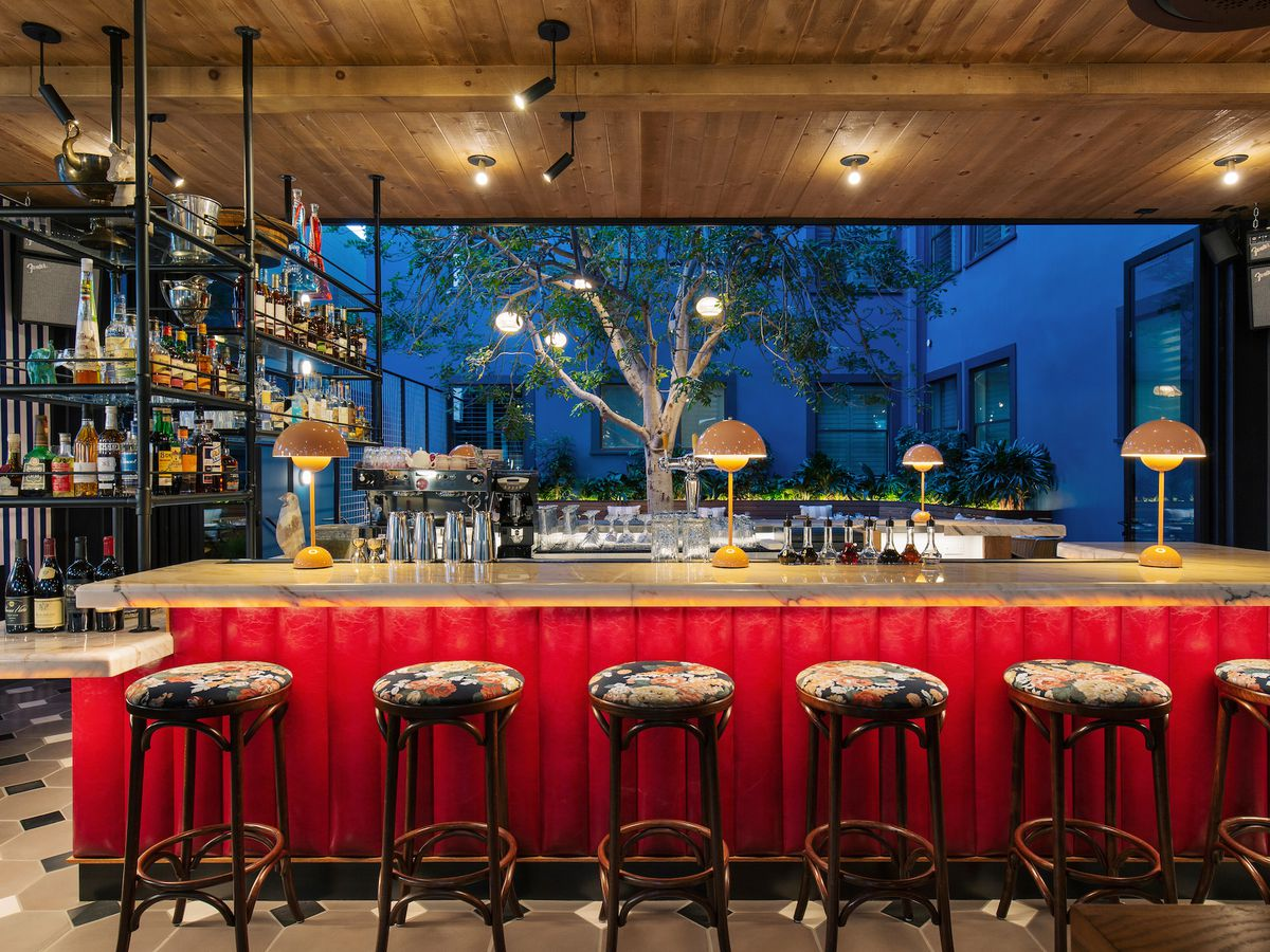 Simonette bar with red underskirt, stools, and blue lights in the distance.