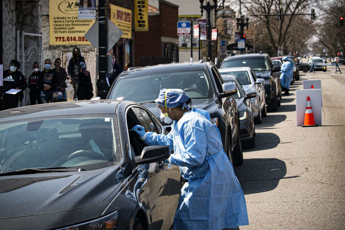 People sit in a line of cars while masked and gowned health care workers approach to test for the coronavirus.