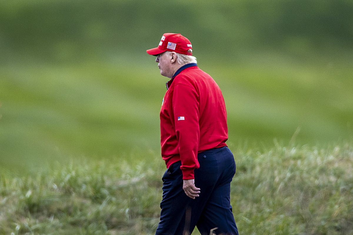 Trump on a golf course in a red jacket and hat.
