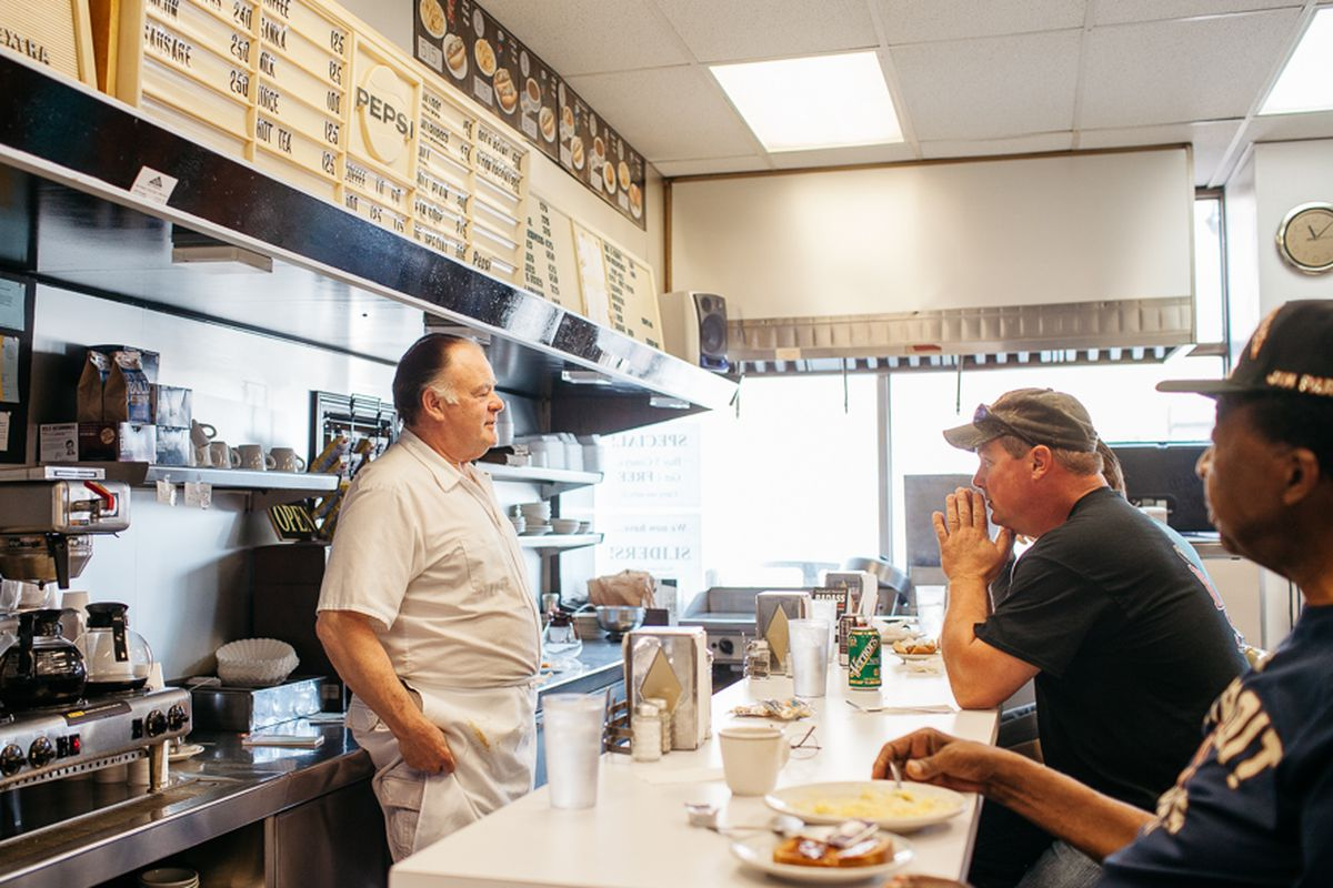 Customers sit at a restaurant lunch counter while a man stands in front, facing them