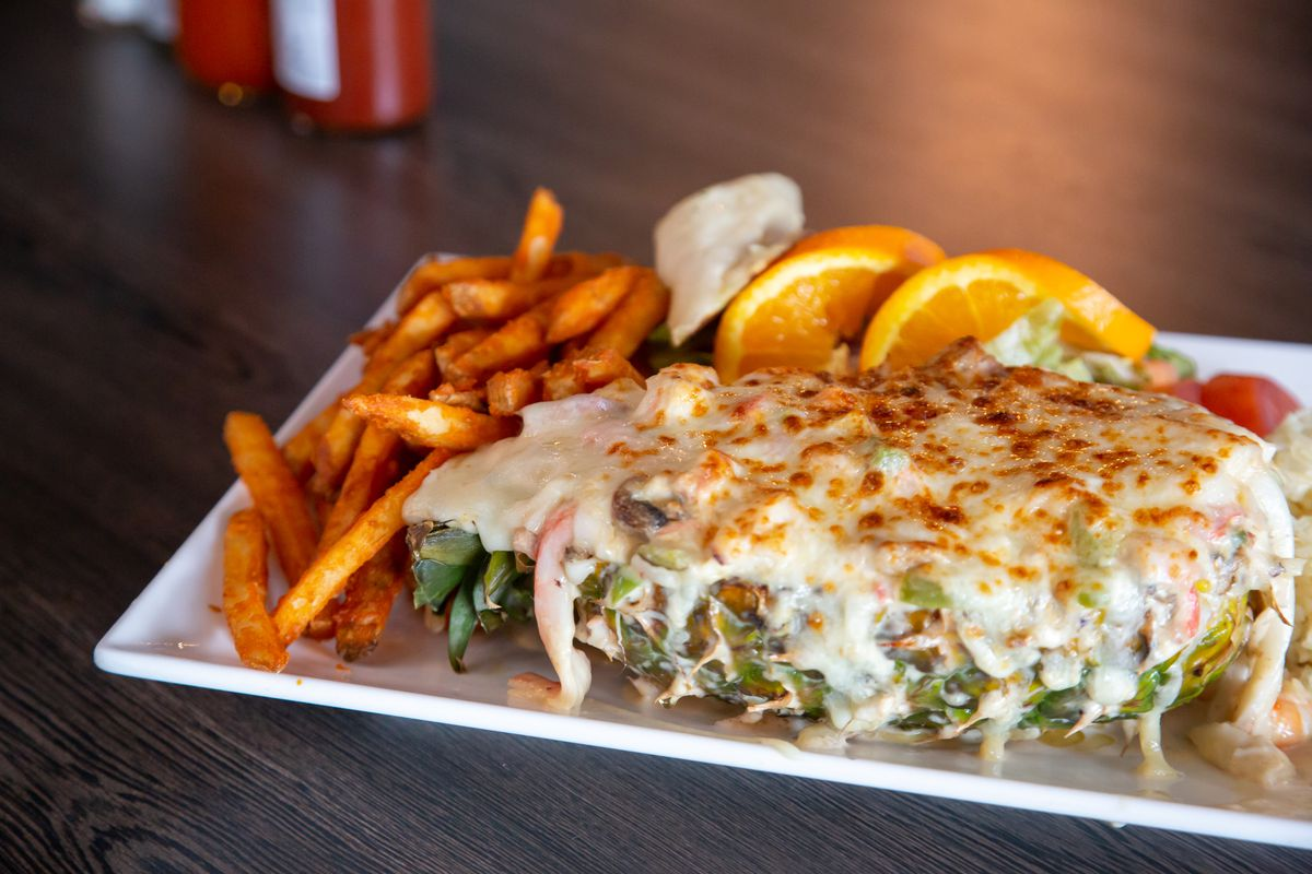 La piña rellena, a half pineapple stuffed with grilled seafood, topped with cheese, and broiled.
