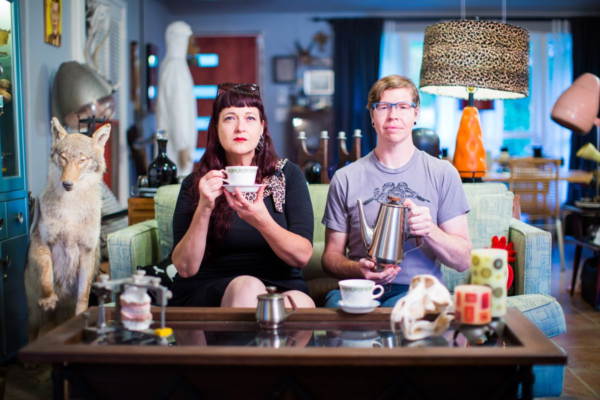 A man and a woman on a couch surrounded by many odd objects