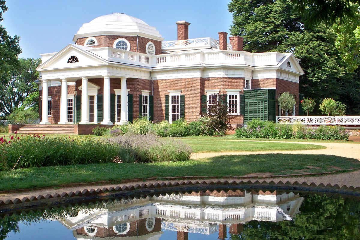 A neo-classical home with covered front porch and dome is clad in brick and topped in white.