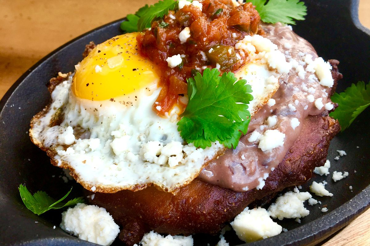 A fried sunny-side up egg sits on a brown-fried doughnut-hole-like hush puppy with a splatter of salsa, a few cilantro leaves, and a crumble of cotija
