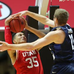Utah Utes forward Kyle Kuzma (35) powers up a shot with Brigham Young Cougars forward Kyle Davis (21) defending as Utah and BYU play in the Huntsman Center in Salt Lake City Wednesday, Dec. 2, 2015.