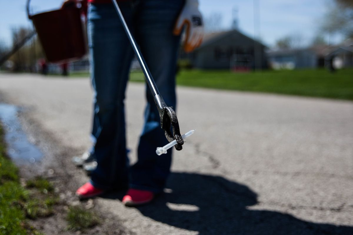 A volunteer picks up a used syringe in Indiana.