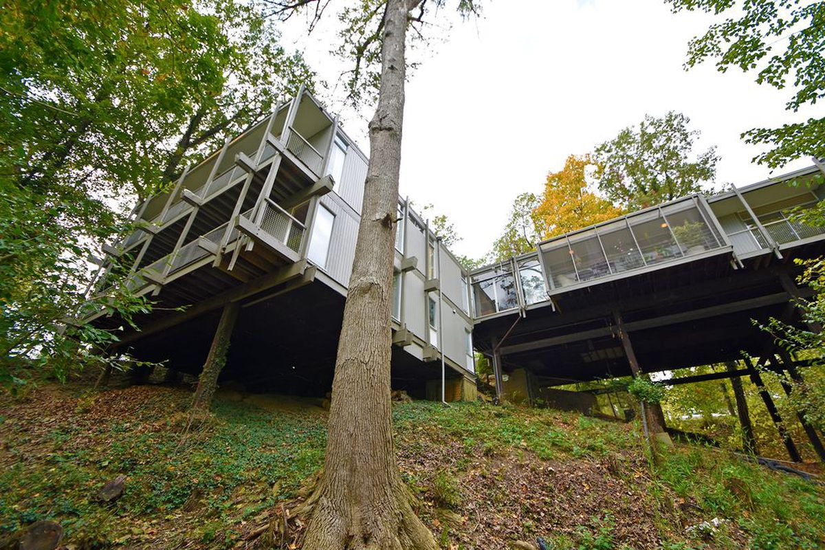 View of a grey-framed linear post-and-beam structure with balconies perching on stilts over a gently sloping hillside.