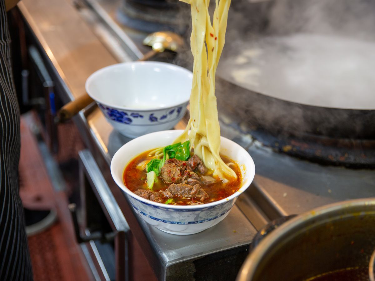 Beef noodle soup with noodles being lifted out of bowl