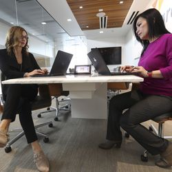 Selma Mlikota, who is on the human resources team at O.C. Tanner, left, works with Hanh Ngo, O.C. Tanner safety manager, at the company's offices in Salt Lake City on Wednesday, Jan. 29, 2020. The Utah firm is a longtime global leader in the employee recognition business, and while it's evolved into an endeavor where software and digital application products outstrip the unique trophies and awards it produces, the company has quietly become a champion on behalf of political refugees who have resettled in Utah.