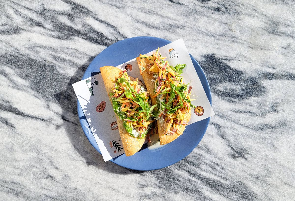 An overhead shot of two long fried tacos on a light blue plate on a marble table.