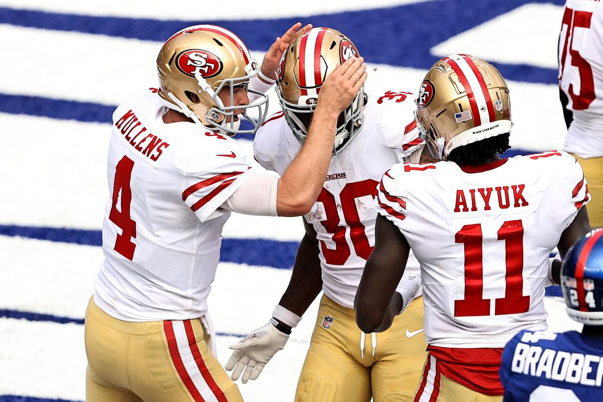 Nick Mullens and Brandon Aiyuk of the San Francisco 49ers congratulate Jeff Wilson Jr. #30 after Wilson Jr. scored a touchdown in the fourth quarter against the New York Giants at MetLife Stadium on September 27, 2020 in East Rutherford, New Jersey.