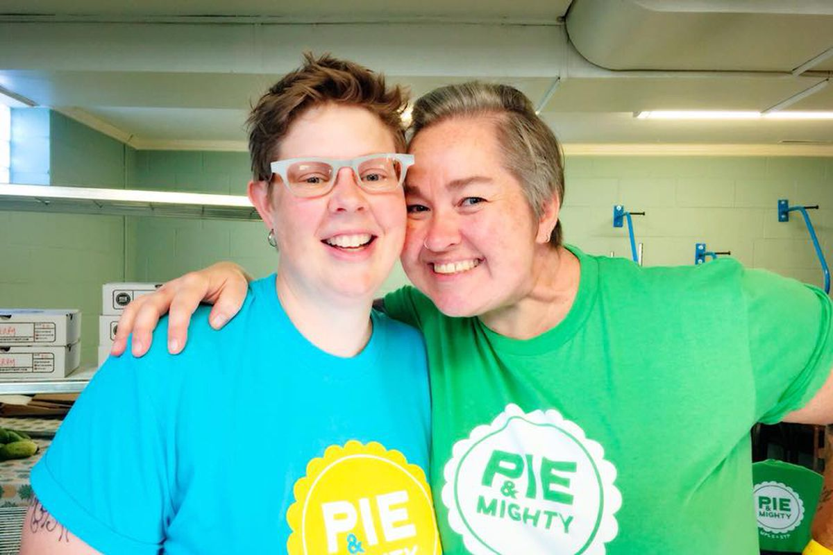 Two women, one in glasses and a blue t-shirt another in a green t-shirt smile and embrace.