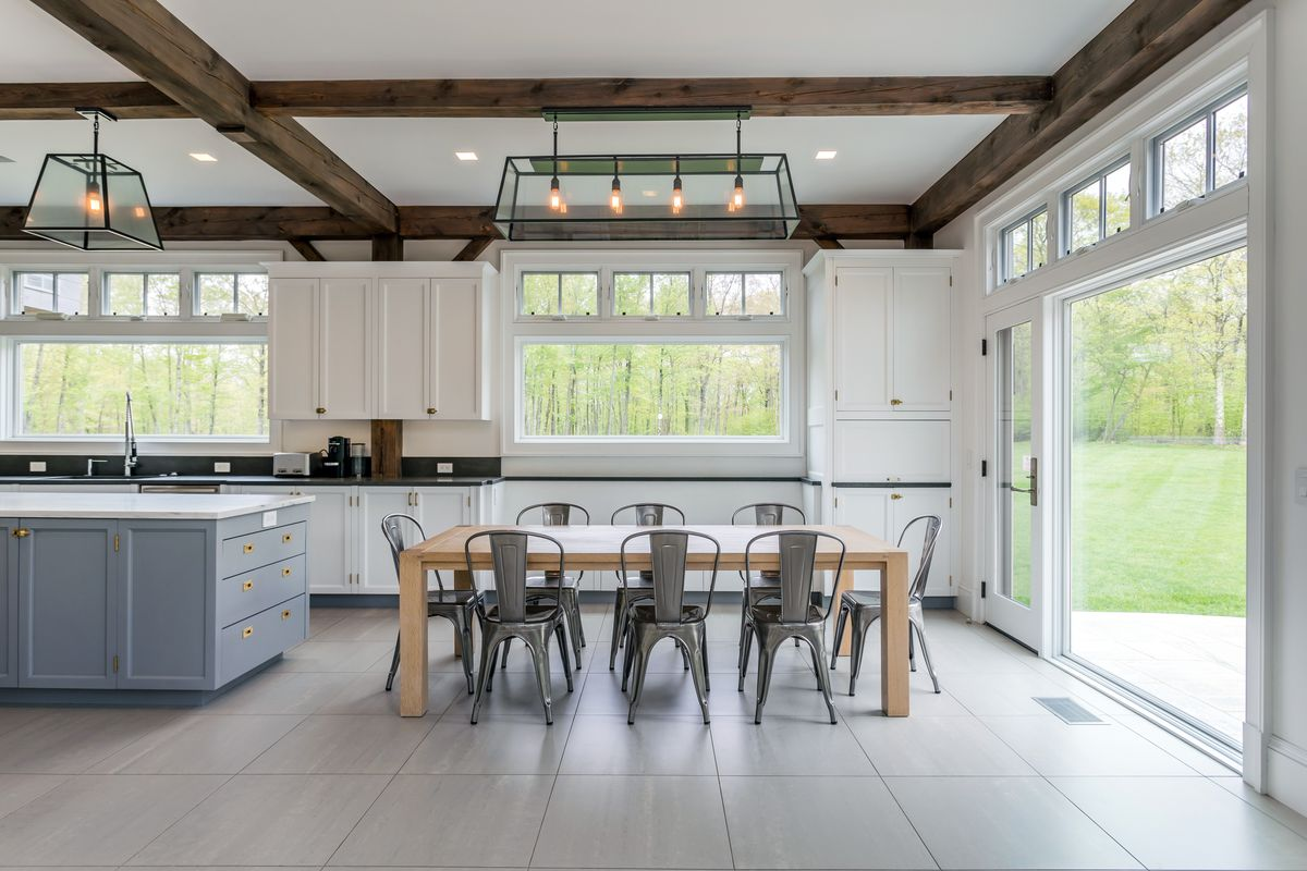 An open concept kitchen and dining room has silver chairs, a wooden table, and white cabinets.