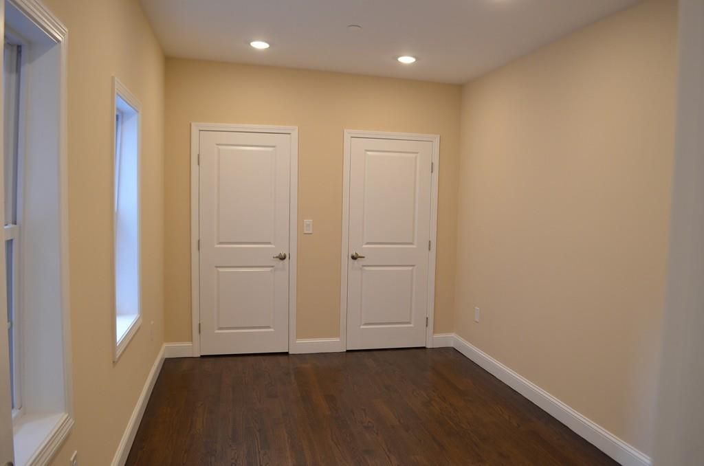An empty, small bedroom with two closed doors at the end.