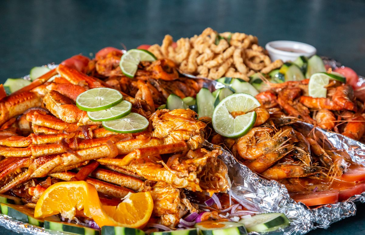 A heaping platter containing crab legs, langoustines or lobster, shrimp, clams, and fried fish