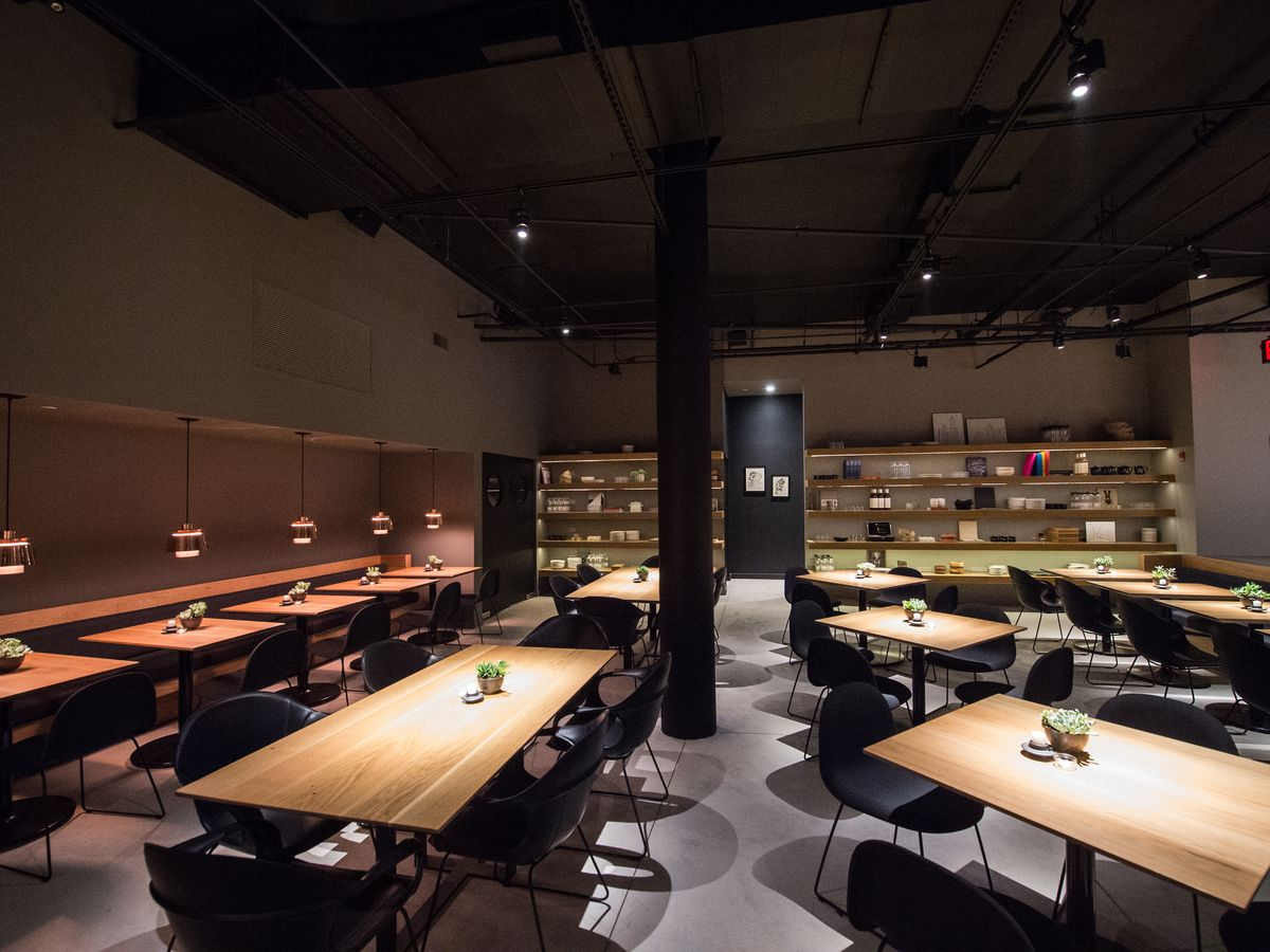 The sleek, dark dining room at Cosme with wooden tables and black walls