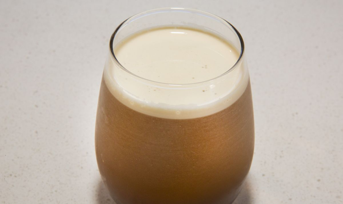 A cold coffee drink with a head of foam in a stemless wine glass.