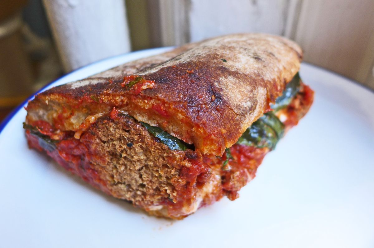 A meatball hero oozing tomato sauce and grease.