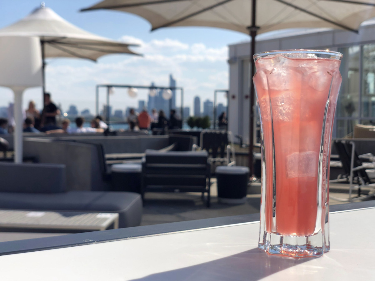 A pink cocktail in a glass with ice is on a patio overlooking the Chicago skyline