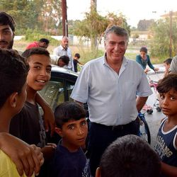 Mayor Iosif-Nampil Morant, center, is surrounded by camp residents at the Kyllini refugee camp in Myrsini, Greece, July 11, 2016. Morant, a native Syrian and the first foreign-born mayor elected in Greece, had the idea to turn the LM Village resort into a refugee camp for families.