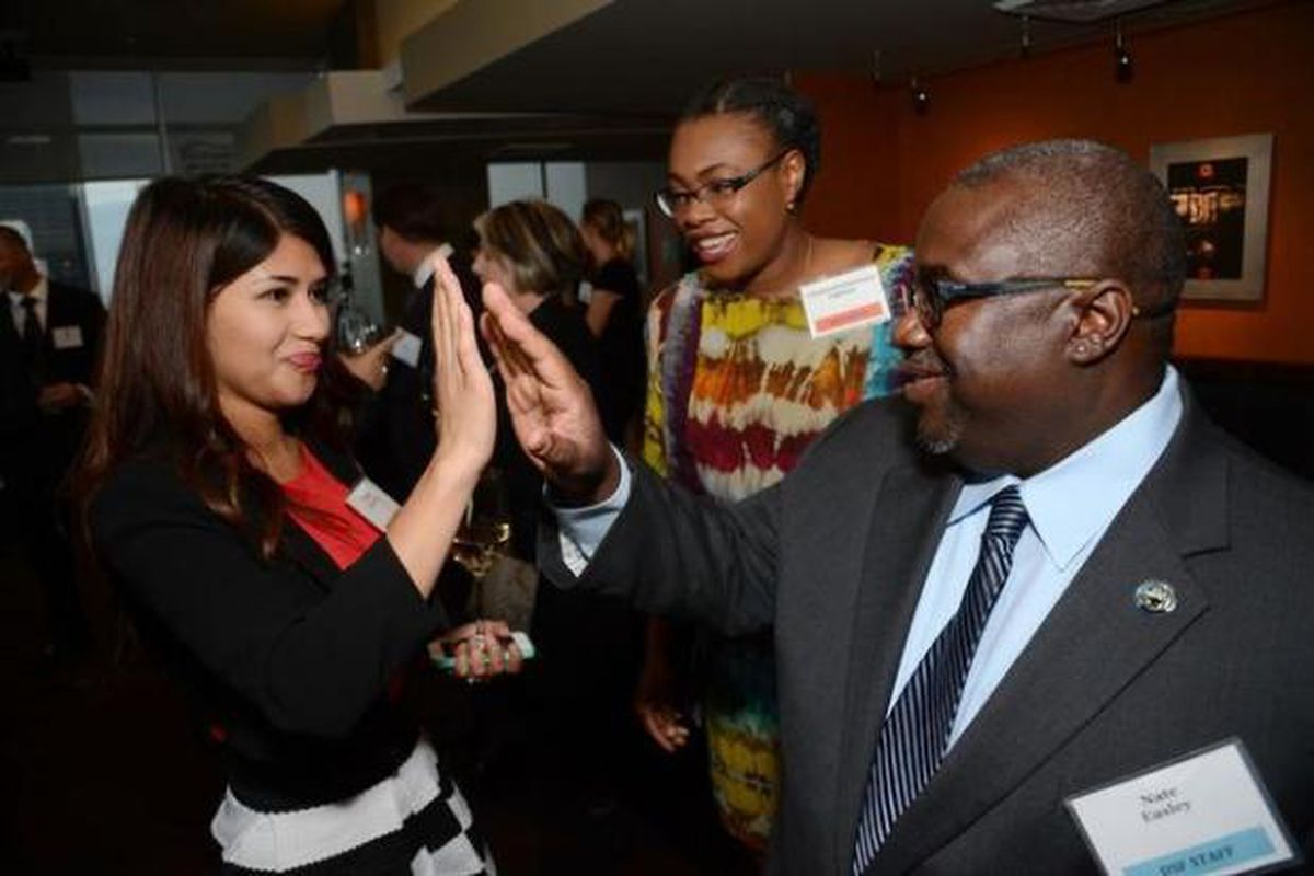 Nate Easley high-fives a Denver Scholarship Foundation alum at an event  in 2015.