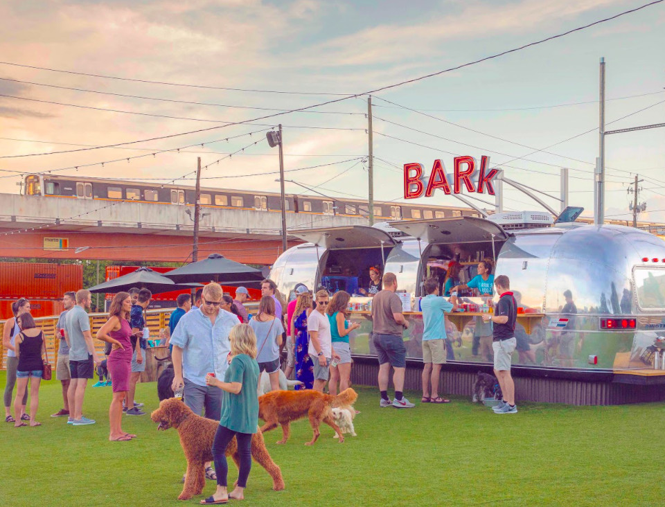 A group of people at dusk in shorts and tee shirts standing in line for the bar inside a silver vintage airstream camper with the word BAR-K in red above it. Three dogs run around their owners
