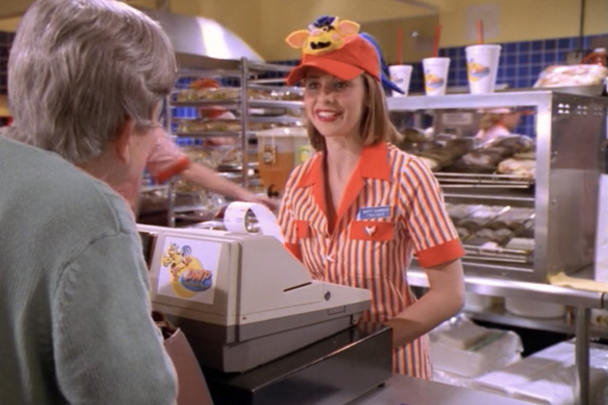 Sarah Michelle Gellar portraying Buffy Summers as she serves an elderly customer while wearing a gaudy orange striped uniform and hat with a cow mascot on it.