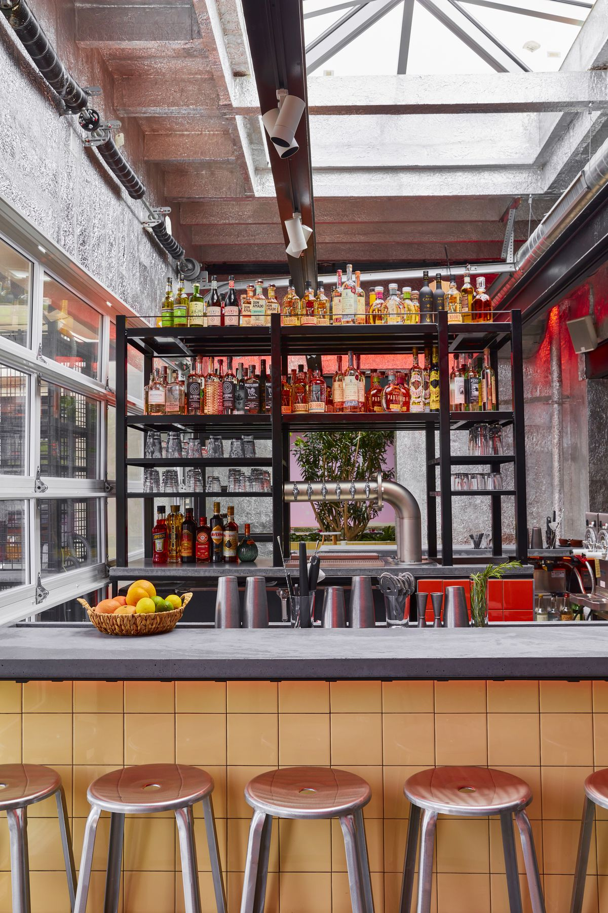 A bar setting with industrial pipes and wooden stools, with an array of liquors and alcohols.
