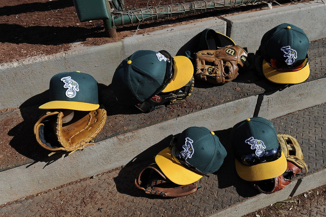 Oakland Athletics players leave their game hats and gloves on the steps of their dugout while playing the Los Angeles Angels during the sixth inning of their Cactus League game at Diablo Stadium in Tempe, Ariz., on Sunday, Feb. 24, 2013. (Jose Carlos Faja